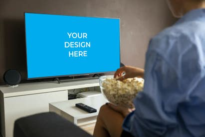 Smart TV on the white TV unit beside the woman eating popcorn