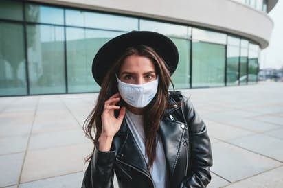 Brunette woman with a hat wearing a face mask