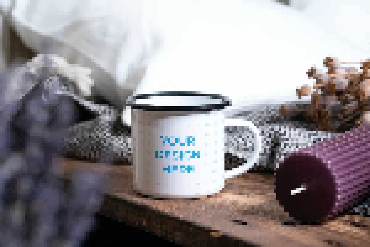 Enamel mug on the wooden table near the candle