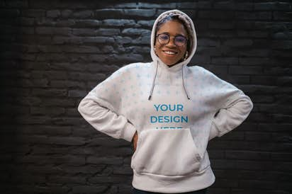 African-American woman with glasses wearing a hoodie near the wall