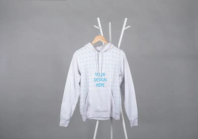 Hoodie on a wooden hanger in front of the gray background