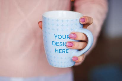 Ceramic mug in the hand of a woman wearing a pink sweater